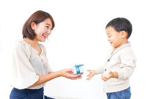 お母さんにプレゼントを渡す子どもの写真素材 [FYI04701912]