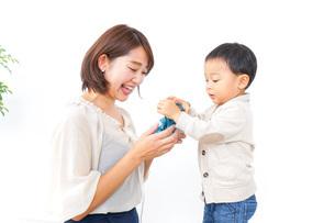 お母さんにプレゼントを渡す子どもの写真素材 [FYI04701916]