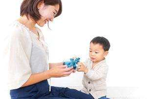 お母さんにプレゼントを渡す子どもの写真素材 [FYI04701917]