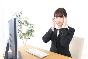 頭痛に苦しむビジネスウーマンの写真素材 [FYI04702559]