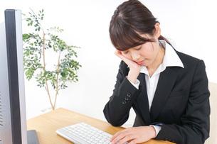 睡眠不足・居眠りをするビジネスウーマンの写真素材 [FYI04702563]