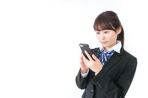 スマホを使う女子高生の写真素材 [FYI04702604]