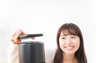 電子マネーで決済をする若い女性の写真素材 [FYI04702706]