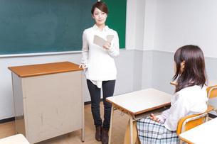 本を持って授業をする女性教師の写真素材 [FYI04703025]