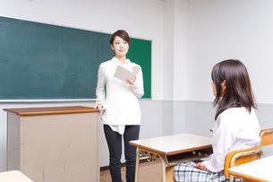 本を持って授業をする女性教師の写真素材 [FYI04703026]