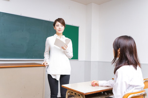 本を持って授業をする女性教師の写真素材 [FYI04703031]