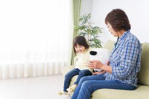 おばあちゃんと遊ぶ小さな子供の写真素材 [FYI04703199]