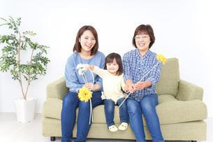 おばあちゃんにお花を渡す子供の写真素材 [FYI04703245]