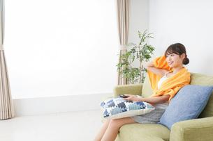 自宅でテレビを見る女性の写真素材 [FYI04703730]