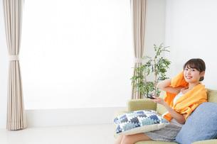 自宅でテレビを見る女性の写真素材 [FYI04703741]