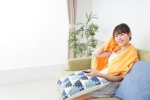 自宅でテレビを見る女性の写真素材 [FYI04703743]