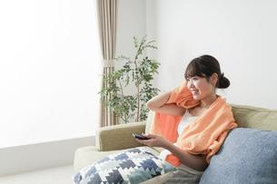 自宅でテレビを見る女性の写真素材 [FYI04703753]