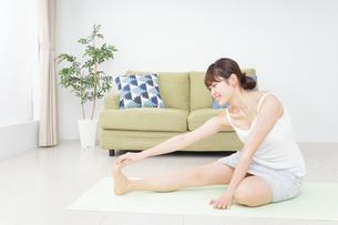 部屋でストレッチをする女性の写真素材 [FYI04703758]