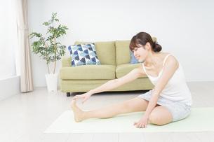 部屋でストレッチをする女性の写真素材 [FYI04703759]