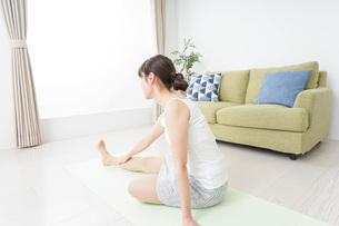 部屋でストレッチをする女性の写真素材 [FYI04703765]