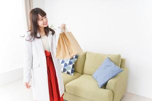 ショッピングから帰ってきた女性の写真素材 [FYI04703799]