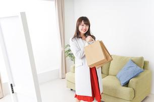 ショッピングから帰ってきた女性の写真素材 [FYI04703803]