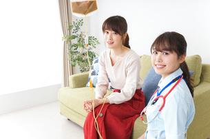 在宅で治療を受ける患者と訪問ナースの写真素材 [FYI04703906]
