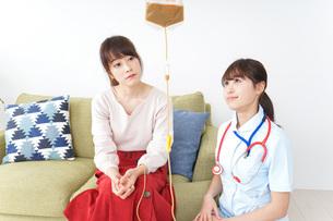 在宅で治療を受ける患者と訪問ナースの写真素材 [FYI04703914]