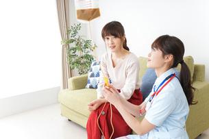 在宅で治療を受ける患者と訪問ナースの写真素材 [FYI04703915]