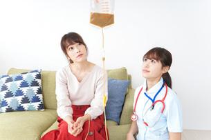 在宅で治療を受ける患者と訪問ナースの写真素材 [FYI04703916]