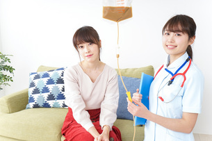 在宅で治療を受ける患者と訪問ナースの写真素材 [FYI04703919]