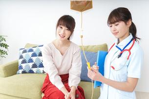 在宅で治療を受ける患者と訪問ナースの写真素材 [FYI04703920]