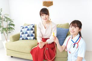 在宅で治療を受ける患者と訪問ナースの写真素材 [FYI04703921]