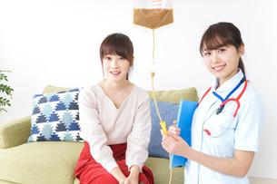 在宅で治療を受ける患者と訪問ナースの写真素材 [FYI04703922]