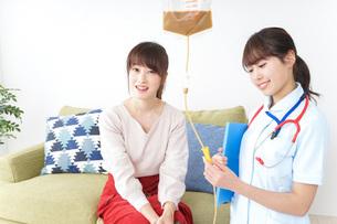 在宅で治療を受ける患者と訪問ナースの写真素材 [FYI04703924]