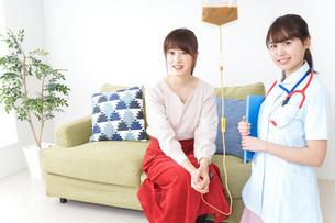 在宅で治療を受ける患者と訪問ナースの写真素材 [FYI04703925]