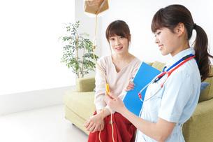 在宅で治療を受ける患者と訪問ナースの写真素材 [FYI04703926]