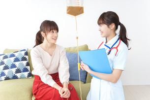 在宅で治療を受ける患者と訪問ナースの写真素材 [FYI04703929]