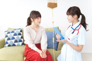 在宅で治療を受ける患者と訪問ナースの写真素材 [FYI04703930]