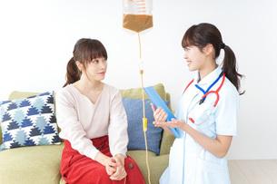 在宅で治療を受ける患者と訪問ナースの写真素材 [FYI04703932]
