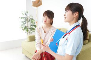 在宅で治療を受ける患者と訪問ナースの写真素材 [FYI04703935]