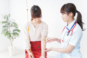 病院で診察を受ける患者とナースの写真素材 [FYI04703942]