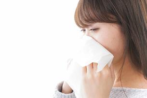 風邪・花粉症で鼻をかむ女性の写真素材 [FYI04704047]