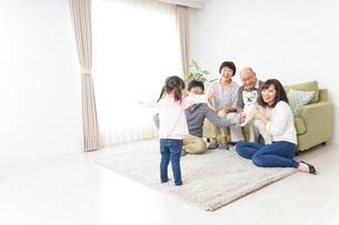 家族で犬と遊ぶ幸せな三世代ファミリーの写真素材 [FYI04704409]