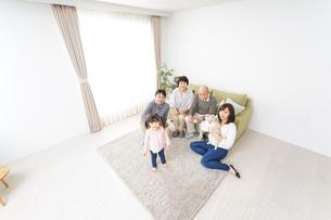家族で犬と遊ぶ幸せな三世代ファミリーの写真素材 [FYI04704431]