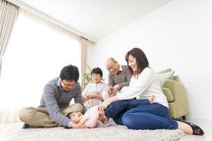 家族で犬と遊ぶ幸せな三世代ファミリーの写真素材 [FYI04704513]