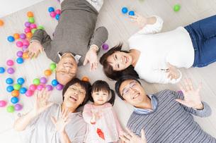 部屋で寝転ぶ三世代の家族の写真素材 [FYI04704794]