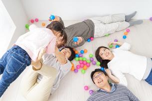 部屋で寝転ぶ三世代の家族の写真素材 [FYI04704799]