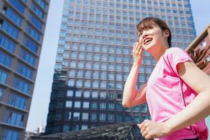 都会でランニングする女性の写真素材 [FYI04705603]