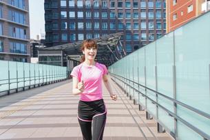 都会でランニングする女性の写真素材 [FYI04705606]