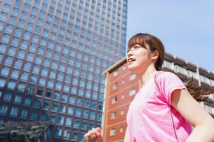 都会でランニングする女性の写真素材 [FYI04705607]