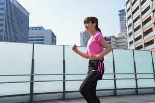 都会でランニングする女性の写真素材 [FYI04705609]