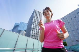 都会でランニングする女性の写真素材 [FYI04705612]