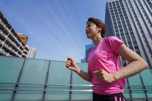 都会でランニングする女性の写真素材 [FYI04705613]