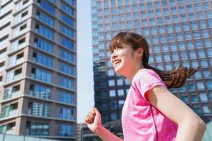 都会でランニングする女性の写真素材 [FYI04705620]